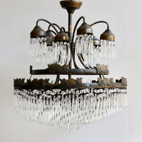 This early 1900s large spiral waterfall chandelier originates from France. This chandelier has ten upper lamps surrounded by glass icicles, the main outer decorative brass circular tier, then further ascending spiral tiers all adorned with glass icicle drops.