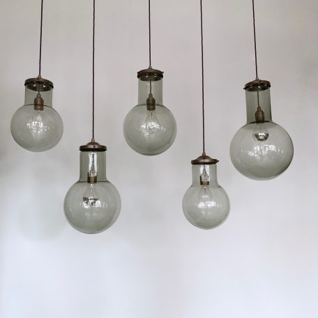 Five unique large grey glass pendants. Wired with antique brass finish fittings and dark blue braided flex.